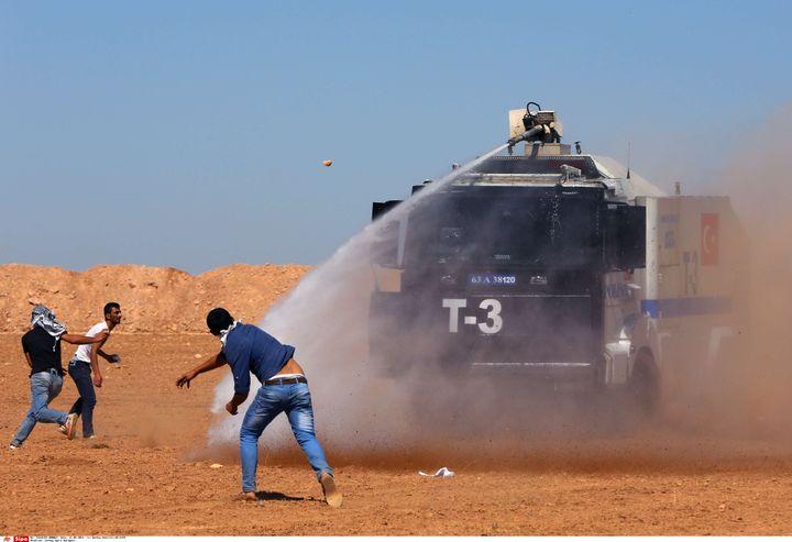 La police turque disperse des manifestants kurdes à proximité de la frontière avec la Syrie, le 21 septembre 2014 près de Suruc (Turquie). (BURHAN OZBILICI / AP / SIPA)