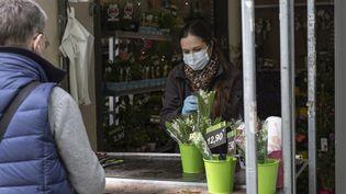 Une fleuriste vend du muguet, à Paris, le 30 avril 2020. (ANTOINE WDOWCZYNSKI / HANS LUCAS / AFP)