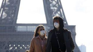 Des touristes portent des masques, non loin de la tour Eiffel, à Paris, le 7 mars 2020. (MEHDI TAAMALLAH / NURPHOTO / AFP)