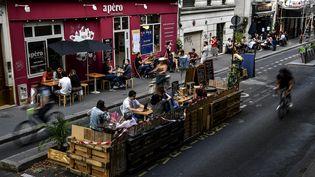 Des personnes prennent un verre à la terrasse d'un café à Paris, le 23 juillet 2020. (CHRISTOPHE ARCHAMBAULT / AFP)