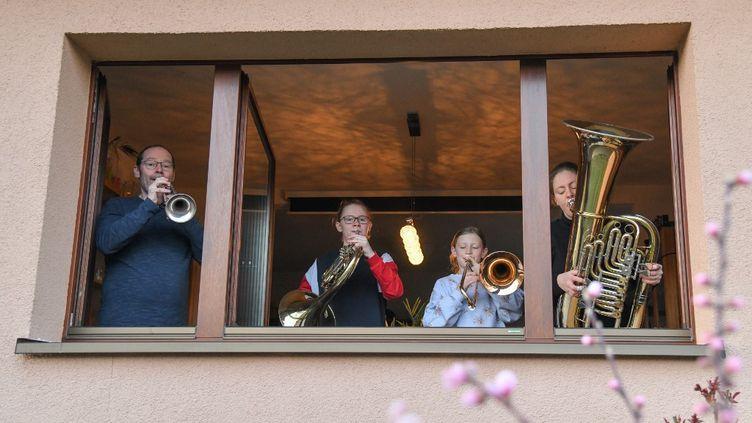 Une famille joue à son balcon pour remercier l'action des soignants. (PATRICK PLEUL / DPA)