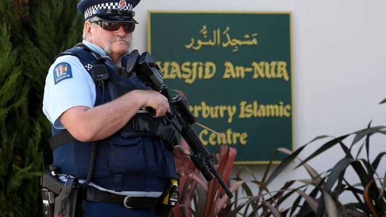 Un policier monte la garde devant la mosquée Al-Noor, à Christchurch, le 29 mars 2019, pendant une cérémonie d'hommage aux victimes des attaques. (SANKA VIDANAGAMA / AFP)