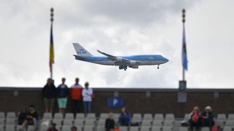 Un Boeing 747 de la compagnie KLM passe près d'un stade, à Amsterdam (illustration). (FABRICE COFFRINI / AFP)