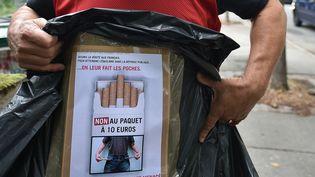 Une pancarte d'unburaliste qui manifeste contre la hausse des prix du tabac, le 17 juillet 2017, à Toulouse (Haute-Garonne). (REMY GABALDA / AFP)