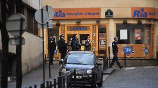 Des policiersautour du commissariat de la Goutte d'Or, où un individua été abattu, jeudi 7 janvier, après avoir tenté d'agresser un policier. (LIONEL BONAVENTURE / AFP)