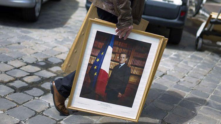 Un employé retire le portrait de Nicolas Sarkozy du palais de l'Elysée, le 15 mai 2012 à Paris. (THIBAULT CAMUS / AP / SIPA / AP)