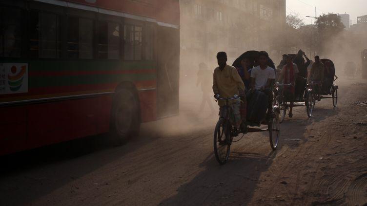 Des habitants se déplacent dans une rue poussiéreuse de Dhaka (Bangladesh), le 1er mars 2020. (SYED MAHAMUDUR RAHMAN / NURPHOTO / AFP)