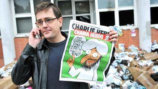 """Charb en 2011, devant les locaux du Charlie Hebdo détruits par un cocktail Molotov. L'incendie était criminel : le journal s'appretait a sortir cette semaine un numero special, rebaptisé pour lÍoccasion """" Charia hebdo"""".  (URMAN LIONEL/SIPA )"""