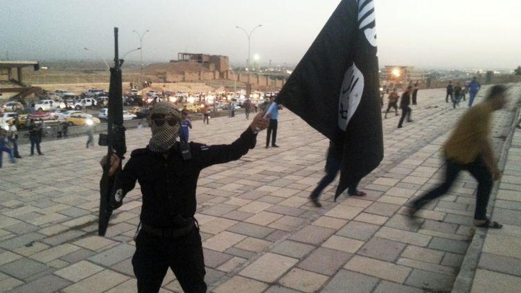 Un combattant de l'Etat islamique brandit une arme et un drapeau dans une rue de Mossoul (Irak) en juin 2014. (REUTERS)