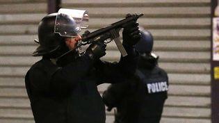 Un policier braquant son arme, le mercredi 18 novembre à Saint-Denis (Seine-Saint-Denis). (FRANCOIS MORI / AP / SIPA)