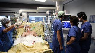 Des médecins surveillent un patient infecté par le Covid-19 et placé en soins intensifs, à l'hôpital Tenon, le 26 janvier 2021, à Paris. (ALAIN JOCARD / AFP)