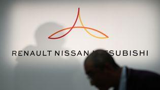 Un membre des médias défile devant un nouveau logo montrant Renault, Nissan et Mitsubishi avant une conférence de presse au siège de Nissan à Yokohama, dans la préfecture de Kanagawa, le 12 mars 2019. (BEHROUZ MEHRI / AFP)