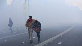 Un couple avance dans une rue de Nantes (Loire-Atlantique) enfumée, après que des incidents ont éclaté lors d'une manifestation en hommage à Rémi Fraisse, le 1er novembre 2014. (  MAXPPP)