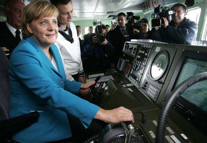 """Angela Merkel écoute les instructions d'un marin à bord de la frégate """"Sachsen"""", sur une base navale de la mer Baltique, le 31 août 2006. (CHRISTIAN CHARISIUS / AFP)"""