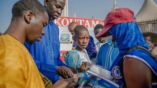 Des Sénégalaisachètent des masques de protection contre le Covid-19 avant d'entrer dans la mosquée Massalikul Jinaan, lors des célébrations de l'Aid al-Fitr, également connu sous le nom de Korite en Afrique de l'Ouest, à Colobane, Dakar, Sénégal, le 13 mai 2021. (CARMEN ABD ALI / AFP)