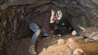 Une bénévole à pied d'oeuvre pour enlever la terre qui empêche l'eau de circuler dans le tunnel (L. Meney / France Télévisions)