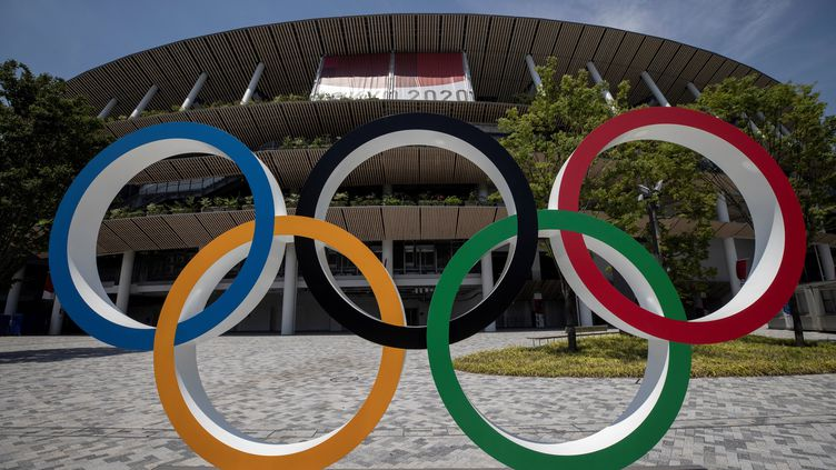 Les anneaux olympiques se sentiront bien seuls ce vendredi 23 juillet, devant le stade olympique de Tokyo, où la cérémonie d'ouverture ne sera vue que par 950 spectateurs en tribunes... mais des centaines de millions à la télévision. (BEHROUZ MEHRI / AFP)