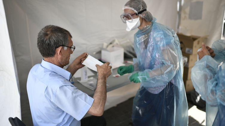 Un habitant de Seine-Saint-Denis testé pour le Covid-19 sur un site de test mobile gratuit à Clichy-sous-Bois le 22 mai 2020. (STEPHANE DE SAKUTIN / AFP)