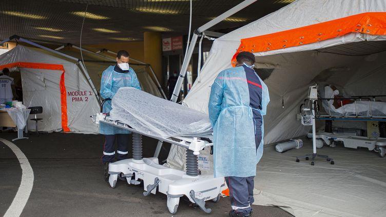 Des sapeurs-pompiers apportent une civière devant une tenteservant à accueillir les malades du Covid-19 en détresse respiratoire devant l'hôpitalPierre Zobda-Quitman de Fort-de-France le 30 juillet 2021. (LIONEL CHAMOISEAU / AFP)