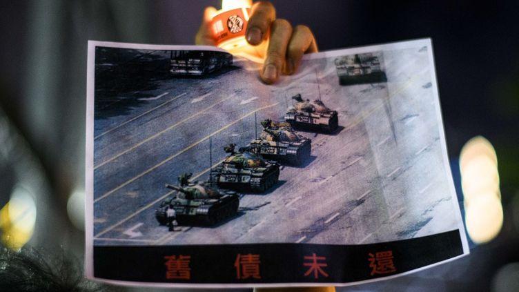 """Un homme tient la célèbre photo de """"l'homme au char"""", le 4 juin 2020, lors d'une commémoration à Hong Kong. (ANTHONY WALLACE / AFP)"""