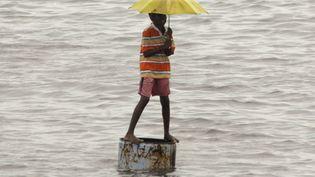 Un enfant réfugié sur un bidon pour échapper à une inondation dans le sud de l'Inde. (reuters/ Babu babu)