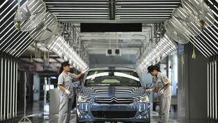Des employés de Dongfeng sur une ligne de production de la nouvelle usine Dongfeng PSA Peugeot Citroën, de Wuhan (Chine). (AFP)