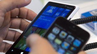 Un homme utilise un téléphone portable, à Paris, le 14 novembre 2012. (FRED DUFOUR / AFP)