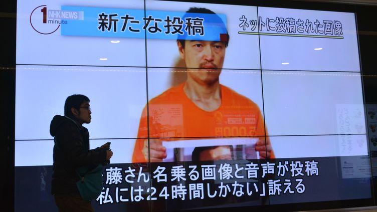 Le visage de l'otage japonais Kenji Goto sur un écran géant dans les rues de Tokyo (Japon), le 28 janvier 2015. (KAZUHIRO NOGI / AFP)