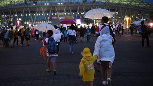 Les supporters de rugby sous la pluie, aux abords du stadeEcopa de Shizuoka, le 11 octobre 2019, avant le match Australie - Géorgie. (ANNE-CHRISTINE POUJOULAT / AFP)