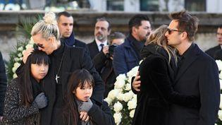 A gauche, Laeticia, Jade et Joy Hallyday ; à droite, David Hallyday et Laura Smet, aux obsèques de Johnny Hallyday, à la Madeleine, à Paris, le 9 décembre 2017. (LUDOVIC MARIN / AFP)