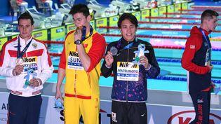 Le nageur chinois Sun Yang (au centre), champion du monde du 200 m nage libre, entourédu JaponaisKatsuhiro Matsumoto, médaille d'argent, et de la médaille de bronze Martin Malyutin. A droite, l'autre médaillé de bronze, le Britannique Duncan Scott ne veut pas apparaître sur la photolors des Mondiaux de natation à Gwangju (Corée du Sud) le 23 juillet 2019. (OLI SCARFF / AFP)
