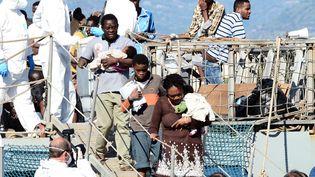 Desmigrants débarquent du navire de la marine irlandaise qui les a secourus, à leur arrivée dans le port de Messine, enSicile(Italie),le 23 juin 2015. (GIOVANNI ISOLINO / CONTROLUCE / AFP)