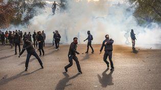 Des manifestants masqués jettent des projectiles en direction de la police, place de la Nation à Paris, après la manifestation contre la loi Travail, le 28 avril 2016. (SIMON GUILLEMIN / AFP)