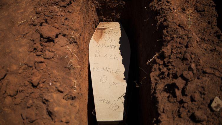 Le cercueil d'une femme noire non identifiée, ainsi qu'il est écrit sur le couvercle, sur le point d'être mis en terre dans le cimetière d'Olifantsvlei, près de Johannesburg, le 27 février 2019. (GUILLEM SARTORIO / AFP)