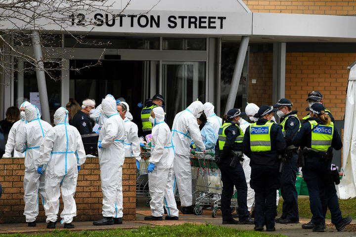 Des pompiers et des policiers se préparent à distribuer de la nourriture dans un immeuble confiné à Melbourne (Australie), le 7 juillet 2020. (STRINGER / REUTERS)
