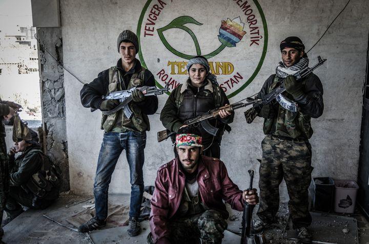 Des combatants kurdes de la milice YPG posent après avoir repris le centre culturel de Kobané, en Syrie, des mains du groupe Etat islamique, le 22 décembre 2014. (JONATHAN RAA / NURPHOTO / AFP)