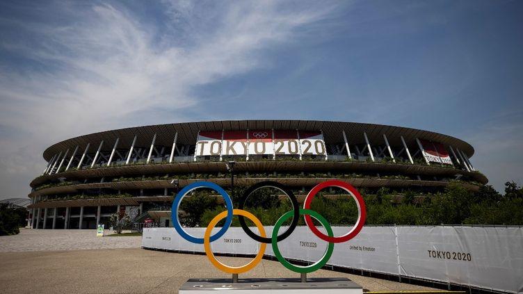 Les anneaux olympiques devant le stade des Jeux de Tokyo, le 20 juillet 2021. (BEHROUZ MEHRI / AFP)