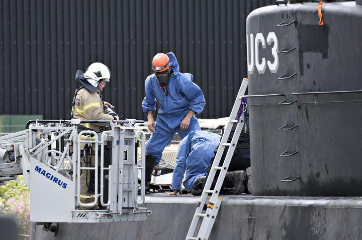 """Des policiers mènent des recherches à bord du """"Nautilus"""", un sous-marin artisanal de 18 mètres de long, dimanche 13 août à Copenhague (Danemark). (JENS NOERGAARD LARSEN / SCANPIX DENMARK)"""