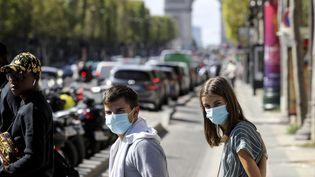 Deux personnesmasquées sur les Champs-Elysées à Paris, le 27 août 2020. (LUDOVIC MARIN / AFP)
