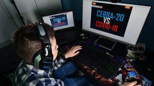 """Lupo Daturi devant le jeu vidéo """"Cerba-20"""" qu'il a créé pour tromper l'ennui pendant le confinement le 24 avril 2020 à Binasco (Italie). (MIGUEL MEDINA / AFP)"""