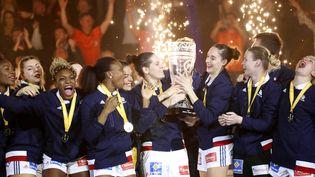 Les joueuses de l'équipe de France de handball lèvent leur trophée de championnes du monde à Hambourg (Allemagne), le 17 décembre 2017 (LAURENT LAIRYS / AFP)