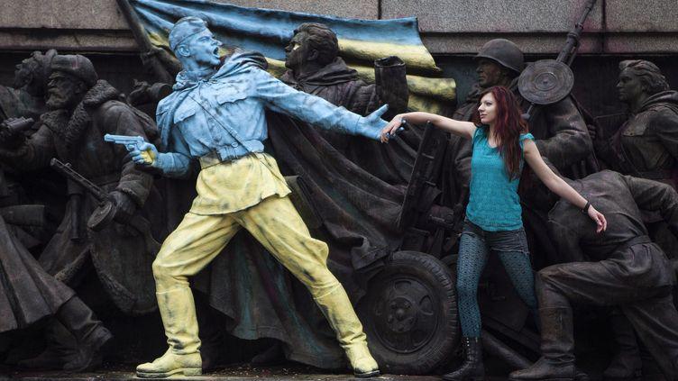 Une femme pose devant un monument représentant des soldats soviétiques et repeint aux couleurs de l'Ukraine à Sofia (Bulgarie), le 23 février 2014. (REUTERS)