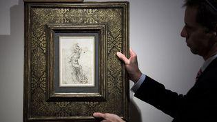 Un membre de la maison de ventes aux enchères Tajan présente un dessin récemment découvert de Léonard de Vinci, le 13 décembre 2016 à Paris. (PHILIPPE LOPEZ / AFP)