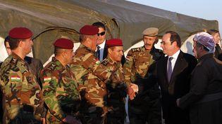François Hollande salue des soldats kurdes peshmergas dans une base située au nord de Mossoul (Irak), lundi 2 janvier 2017, en compagnie du président de la région autonome Massoud Barzani (à droite). (CHRISTOPHE ENA / POOL / AFP)