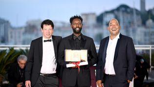 Ladj Ly (au centre) accompagné des producteurs Christophe Barral (à gauche) et Toufik Ayadi (à droite), lors de la remise des prix de la 72e édition du festival de Cannes, le 25 mai 2019. (LOIC VENANCE / AFP)