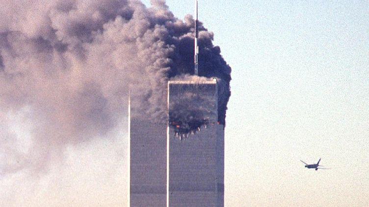 Un des avions de ligne piratés par les terroristes d'Al-Qaïda vole en direction des Twin Towers du World Trade Center le 11 septembre 2001 à New York (Etats-Unis). (SETH MCALLISTER / AFP)