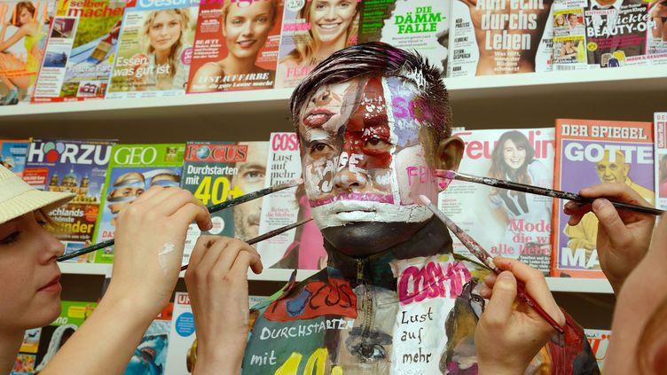 L'artiste chinois Liu Bolin en train de se fondre dans un kiosque à journaux, en Allemagne, en 2013.  (Bernd Weissbrod / EPA / MaxPPP)