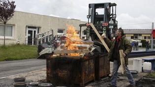 Un employé de l'usine GM&S dans la Creuse participe à la destruction du matériel, le 11 mai 2017. (PASCAL LACHENAUD / AFP)