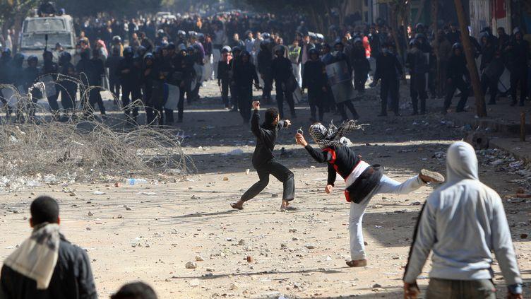 Des manifestants jettent des pierres sur la police anti-émeute le 5 février 2012 au Caire (Egypte). (MAHMUD HAMS / AFP)