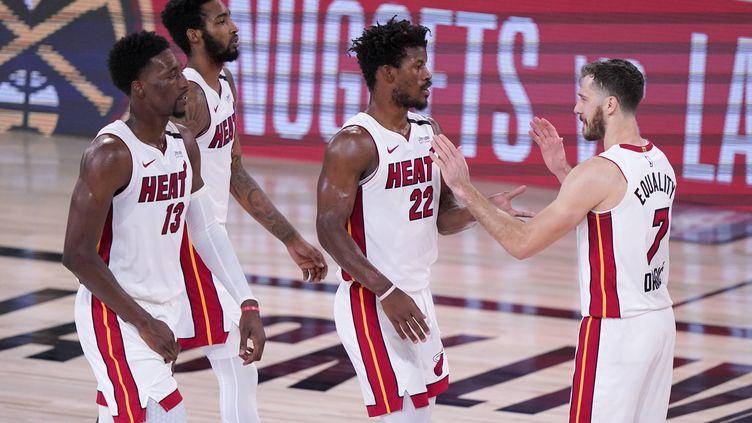 Bam Adebayo, Derrick Jones Jr, Jimmy Butler, et Goran Dragic des Heat de Miami célèbrent leur victoire contre les Celtics de Boston, le jeudi 17 septembre, à Lake Buena Vista, en Floride. (MARK J. TERRILL/AP/SIPA / SIPA)